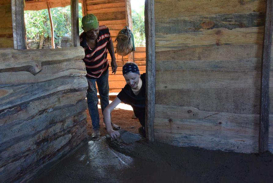 Paikallinen mies opastaa Amanda Tilvikselle, miten sementtiä tasoitetaan. Kosteassa ilmastossa rakentaminen on kevyttä. Rakenteilla oleva talo on tyypillinen maaseudun talo.
