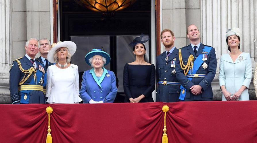 Kuningasperhe yhteispotretissa kesältä 2018: prinssi Charles, prinssi Andrew, herttuatar Camilla, kuningatar Elisabet II, herttuatar Meghan, prinssi ja Sussexin herttua Harry, prinssi ja Cambridgen herttua William sekä herttuatar Catherine hymyilevät Buckinghamin palatsin parvekkeella Lontoossa.