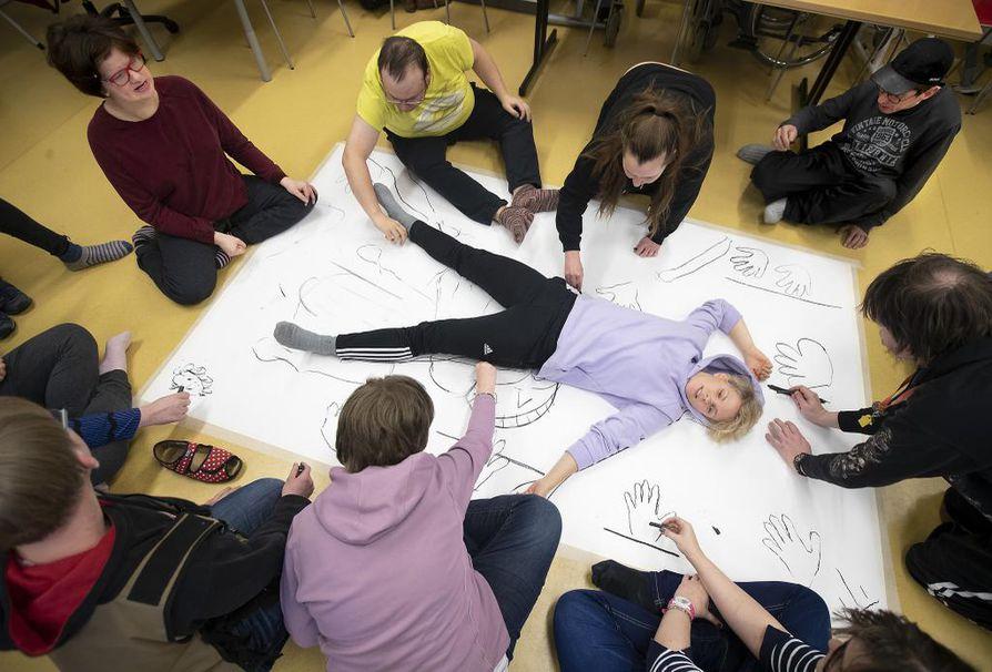 Toimintakeskus Zytykkeessä Kempeleessä piirrettiin ja maalattiin porukalla Saunalaulun lavastetta. Ääriviivapiirrosta varten paperilla makasi äksänä projektin vetäjä, tanssitaiteilija Laura Sorvari Helsingistä.