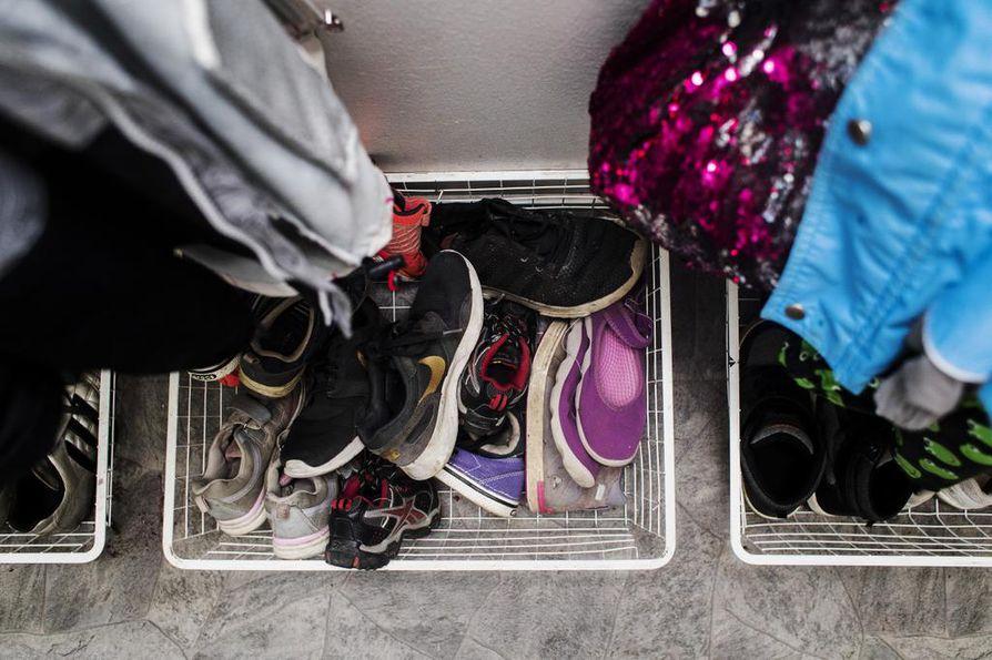 Lattialla olevissa kenkäkoreissa on kahden lapsen kengät.