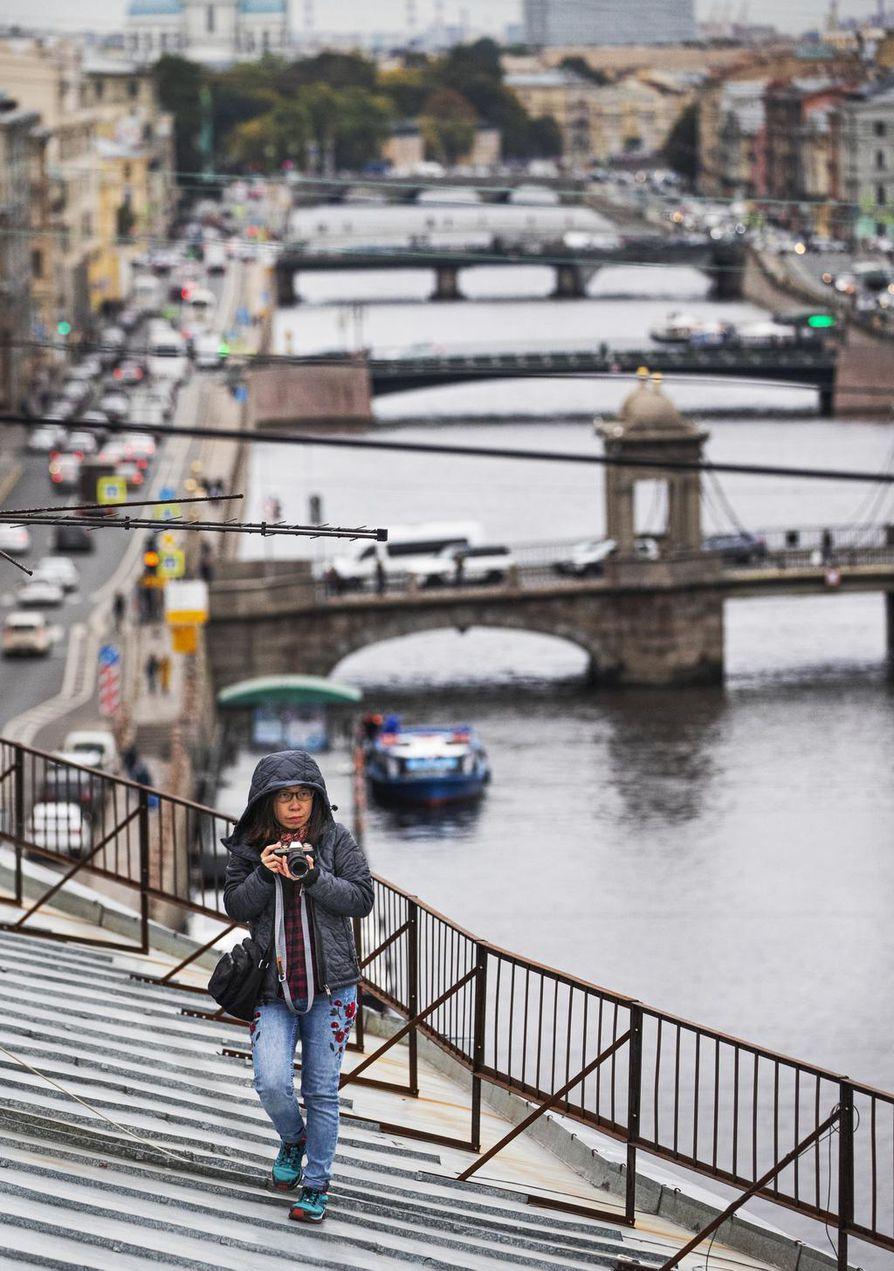 Taustalla näkyvät Fontankan sillat houkuttelivat vietnamilaisen turistin Pietarissa opastetulle kattokierrokselle.