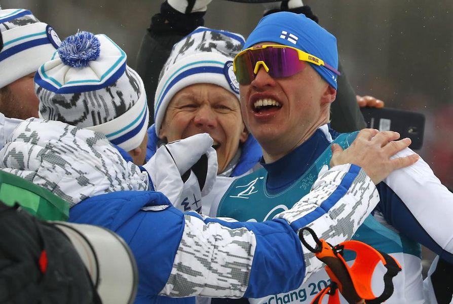 Suomen huoltojoukot ja valmentajat onnittelivat Iivo Niskasta kultahiihdon jälkeen.