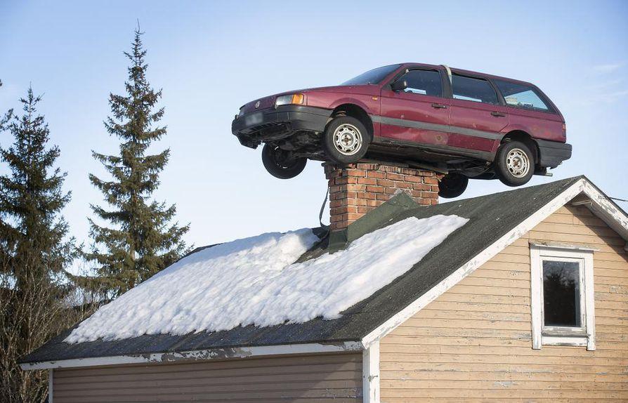 Yli-Iissä maalaistalon katolle piipun päälle on nostettu farmariauto.