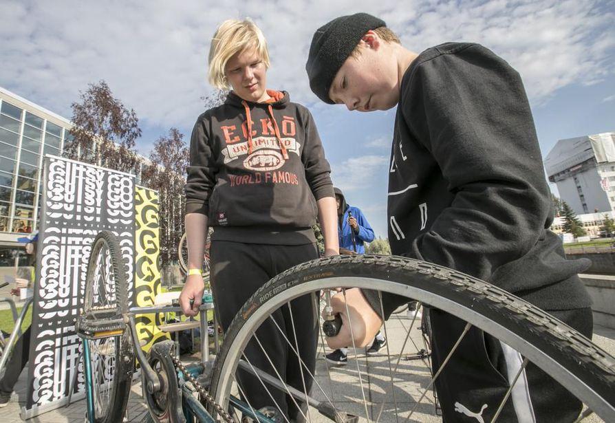 Sampo Jylhä (vas.) ja Tommy Kumpula Myllytullin koulusta huoltamassa pyörää Anna pyöräni pyöriä -pienryhmässä pääkirjaston edessä.
