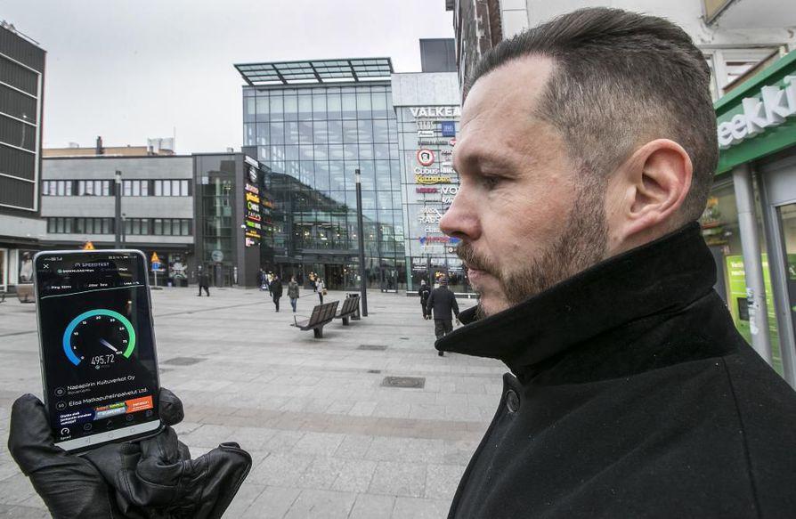 Elisan aluejohtaja Jarmo Mikkola esittelee viime viikolla avatun 5G-verkon nopeuksia Isollakadulla. Verkon säätöjen ollessa vielä kesken 5G:n latausnopeudet ovat kyseisessä paikassa nelisen kertaa suuremmat kuin Elisan 4G:llä.