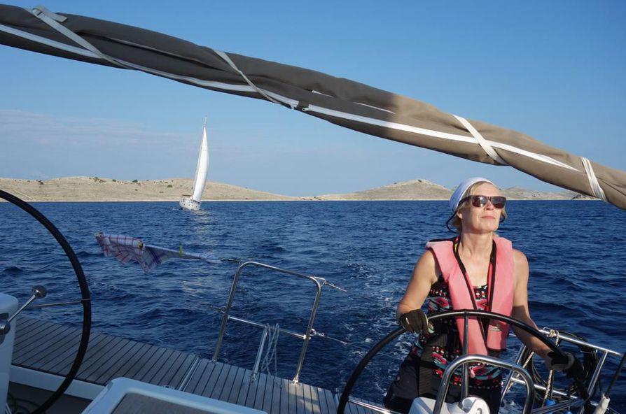 Liisa Palmroth ruorissa luoviosuudella Kornatin saaristossa. Kaksi ruoria helpottaa ohjausta ja liikkumista veneessä. Keittiöpyyhkeet kuivuvat nopeasti tuulessa.